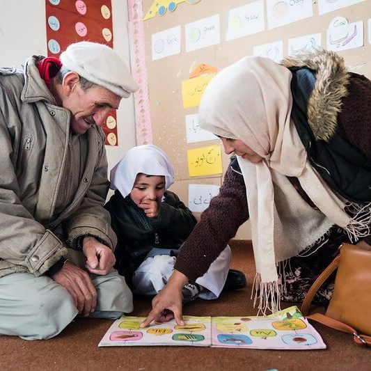 a grandfather and granddaughter sit with a teacher showing them a book.
