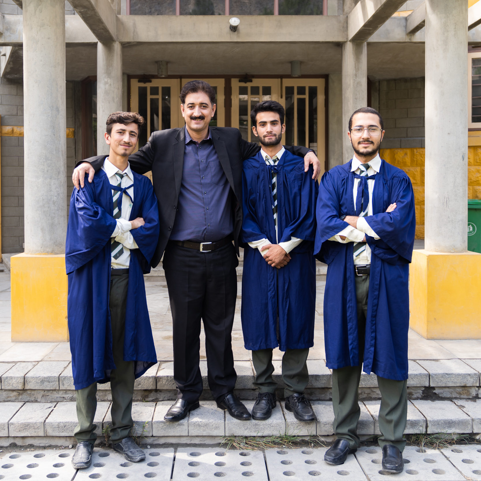 three young men wearing graduation gowns stand with a teacher outside a modern school building