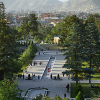 People are shown walking in a park with a city in the background