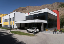 """The front of a hospital building with an SUV in front and mountains in the background. """"Aga Khan Medical Centre"""" is on the top of the hospital."""