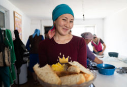 Woman holds out plate of bread as others work in the backgroun