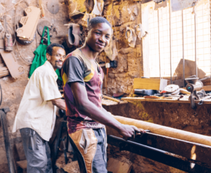 Economic Inclusion: A young Kenyan man works in a carpentry shop.