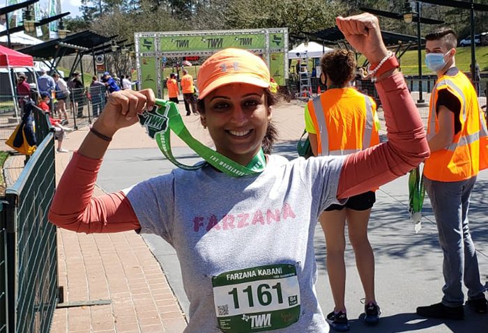 AKF USA supporter Farzana holds up her medal while wearing a racing bib