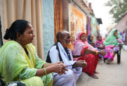 Residents of Patna, India sit in front of their homes and discuss the need for sanitation facilities
