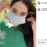 An Instagram screenshot shows a video frame of a woman putting a mask on over her nose and mouth. The Instagram caption is #AKAH#covid19#besafe 🌿