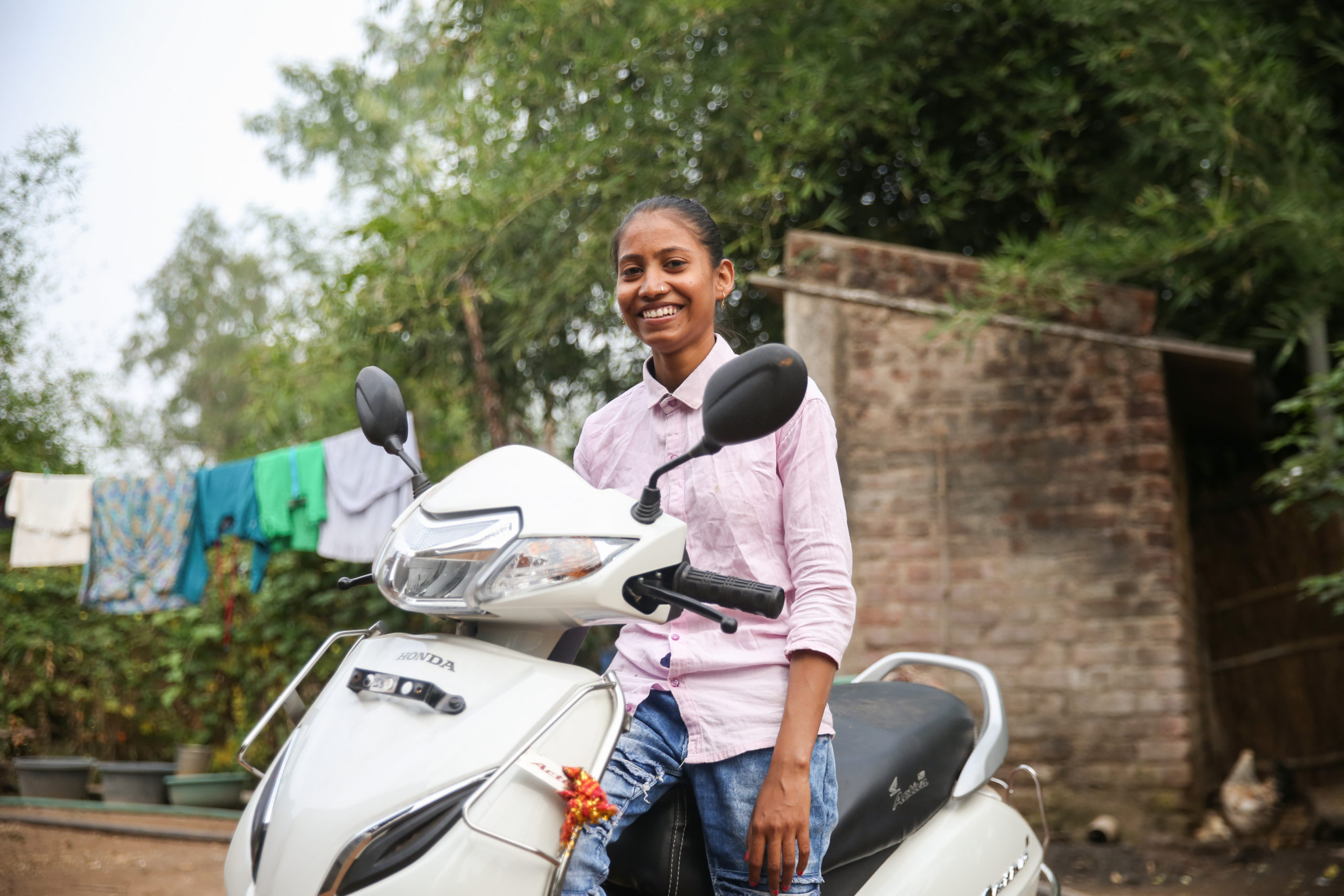 Girl smiles as she sits on a scooter
