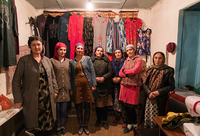 Women stand below the clothes they have sewn